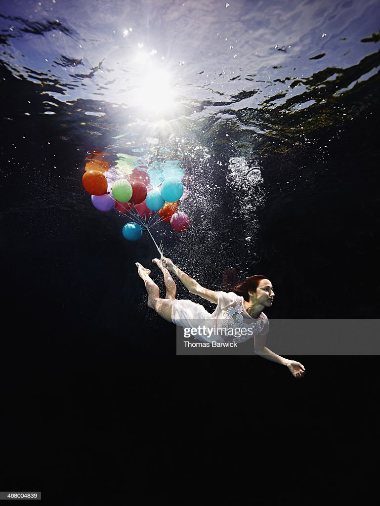 View from underwater of woman holding balloons : Stock Photo