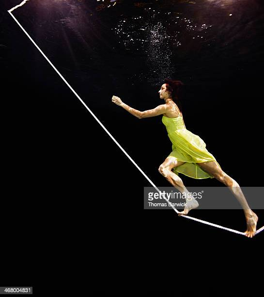 View from underwater of woman walking up tightrope