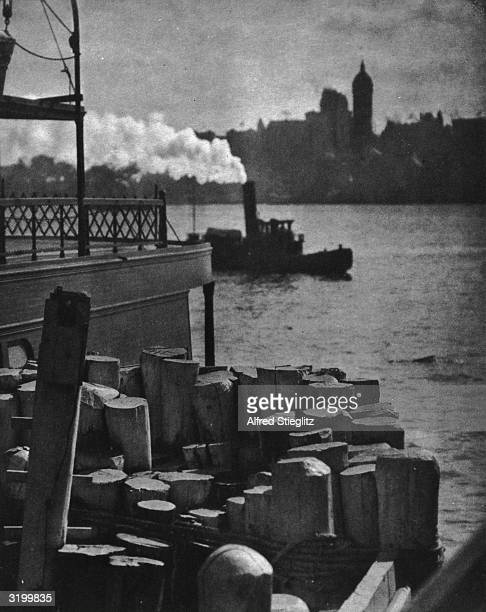 View from wooden mooring posts of a tugboat sailing along the East River past a backdrop of lower Manhattan New York City