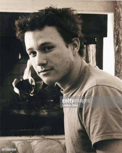 View in sepia tone of Heath Ledger as he takes a break from festivities to rest on a hearth before a fireplace in a condominium during the Sundance...