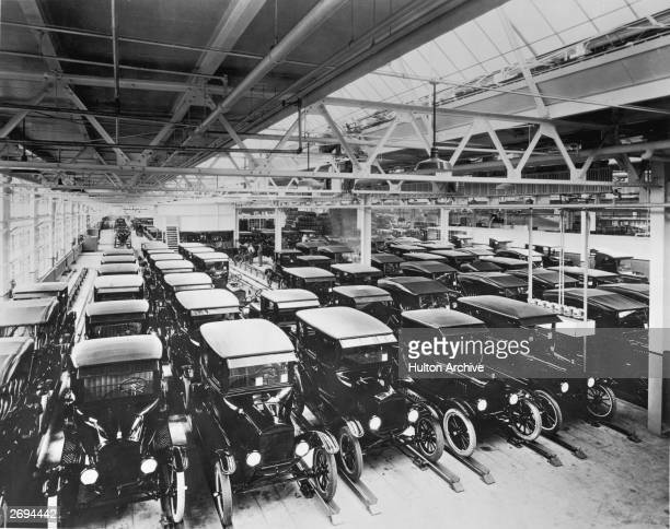 A view inside the Ford Motor Company factory with rows of new Model T motor cars