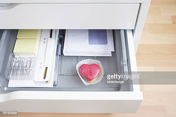 view into open desk drawer containing little cake in shape of heart