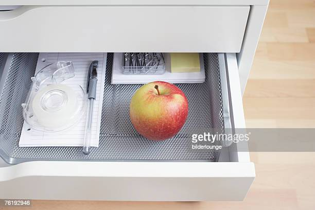 view into open desk drawer containing red apple