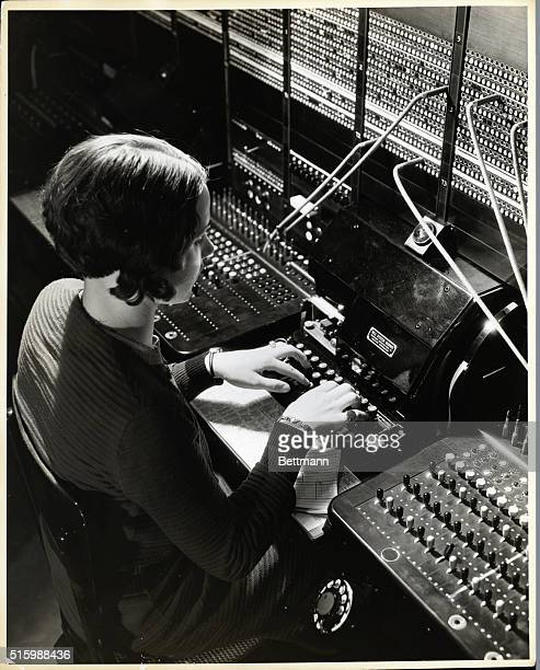 A view looking down at a teletype operator as she types in code Undated photograph