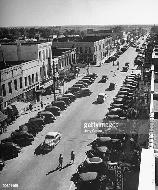 A view looking down on Commercial St of Lebanon with cars parked on both sides of a street and pedestrian walking along while shopping