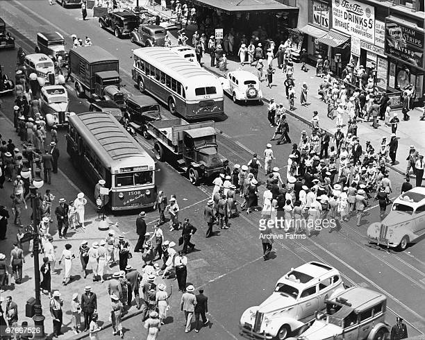 View looking down onto the pedestrian and vehicular traffic on the busy intersection of 34th Street and Broadway off Herald Square 1936 People can be...