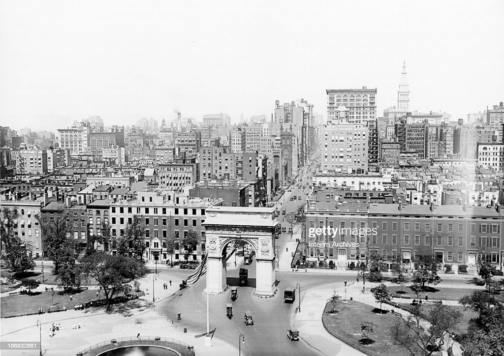 View looking north at Washington Square Park with traffic visible as it enters through the arch off Fifth Avenue New York ca 1920