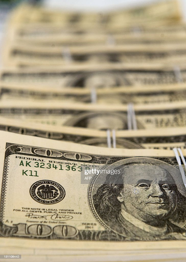 View of 100 dollars notes, part of 1,1 million forged dollars seized by the National Police, on display during a press conference in Cali, department of Valle del Cauca , Colombia, on November 1, 2011. AFP PHOTO/Luis ROBAYO