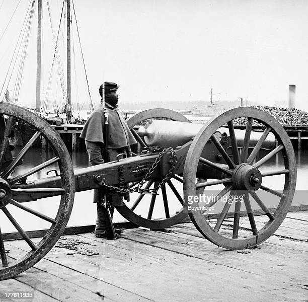 View of a 12 pound Napoleon Cannon artillery piece guarded by an African American soldier on a wharf