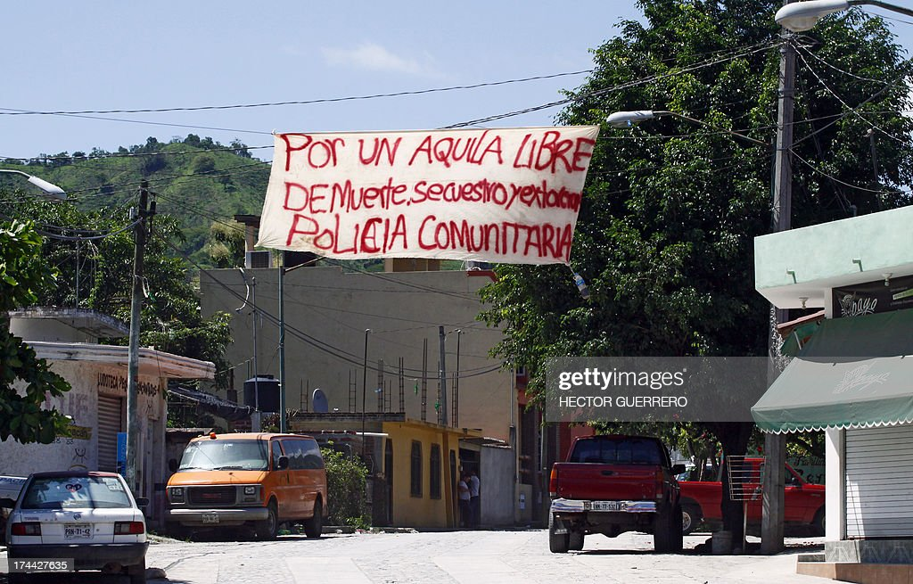 View of a banner reading 'For an Aquila free from death, kidnapping, and extortion. Community police' in Aquila, Michoacan State, Mexico on July 25, 2013. A new group of armed residents settled in recent days to protect the community from organized crime. AFP PHOTO/Hector Guerrero