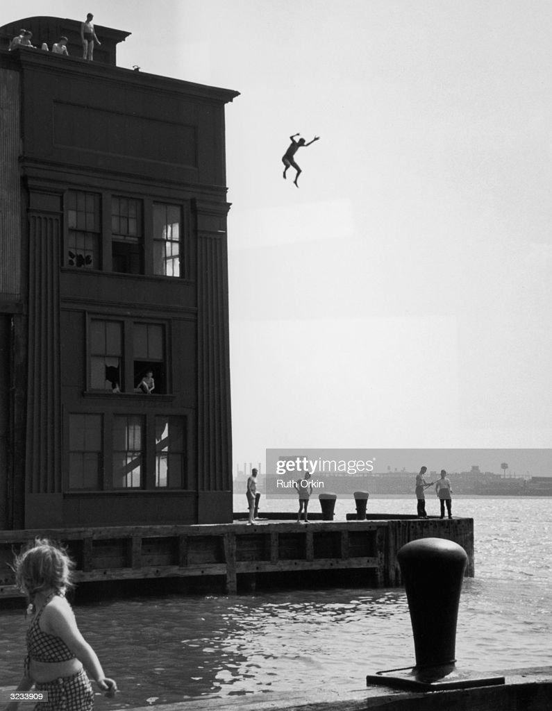 View of a boy falling in midair after jumping from the roof of a derelict building into the Hudson River, New York City, NY.