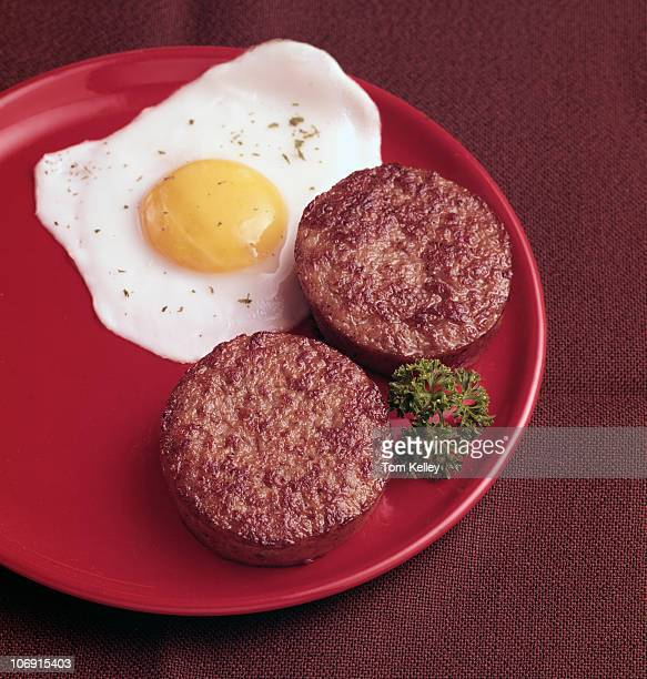 View of a breakfast consisting of an egg and two sausage patties on a red plate seen against a brown background 1985