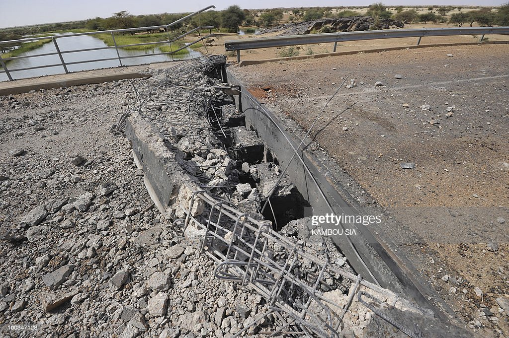View of a bridge blown up by the Movement for Jihad and Oneness (MUJAO) near Ansongo, a town south of the northern Malian city of Gao on January 29, 2013. Troops from Niger and Mali on January 29 entered Ansongo, which along with Gao was recaptured by French-led soldiers over the weekend in a lightning offensive against radicals holding Mali's north. So far, just 2,000 African troops have been sent to Mali or neighboring Niger, many of them from Chad, to boost the French-led offensive which began on January 11 and led to the recapture of several towns, including Ansongo. AFP PHOTO / KAMBOU SIA