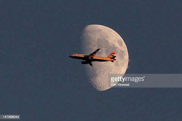 A view of a British Airways plane flying past the moon over day four of the Wimbledon Lawn Tennis Championships at the All England Lawn Tennis and...