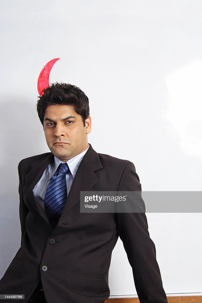 View of a business man with horn on head : Stock Photo