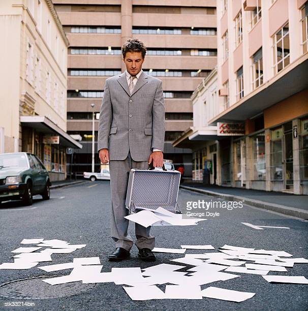 view of a businessman standing on a street with contents of his briefcase spilt out