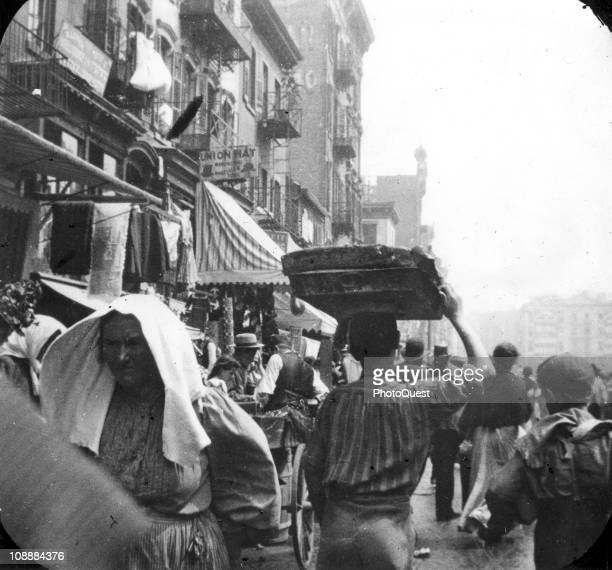 View of a busy street scene probably in the Lower East Side neighborhood of New York showing a pedestrian carrying bread on a tray balanced upon his...