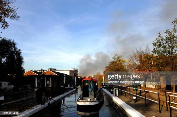View of a canal boat as smoke bellows from a fire in Stratford east London Firefighters are dealing with a blaze today in Waterden Road Stratford an...