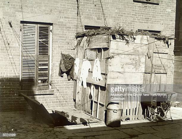 View of a clothesline and a sewing machine standing in front of a makeshift wooden shack in the backyard of a tenement building New York City