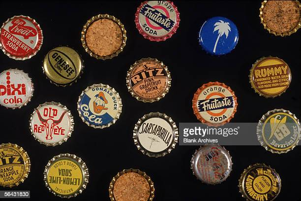 View of a collection of bottle caps some with cork undersides 1950s Pictured caps include Big Treat Strawberry Soda Pixi Cola Genesee Beer Old Red...