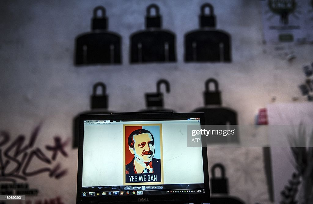 A view of a computer screen showing a digital portrait of the Turkish Prime Minister Recep Tayyip Erdogan and text reading 'Yes we ban' on a laptop...