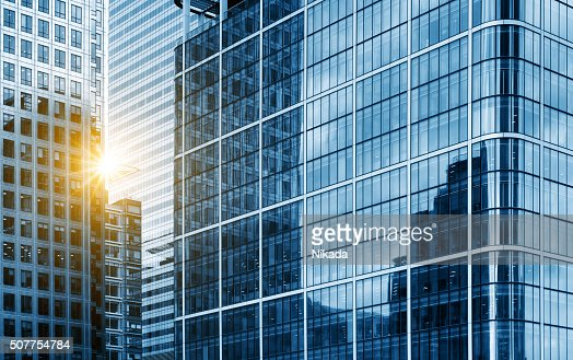 view of a contemporary glass skyscraper reflecting the blue sky