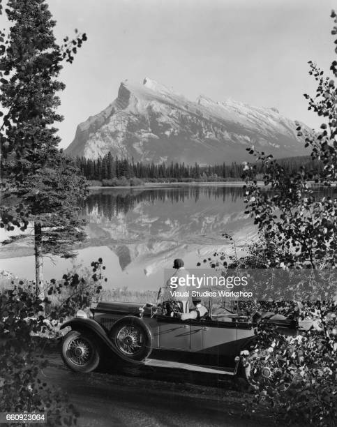 View of a couple in a convertible car parked alongside Vermilion Lake in Banff National Park Alberta Canada 1920s or 1930s In the background is Mount...