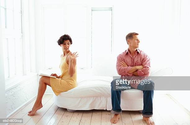 view of a couple sitting apart and having a disagreement