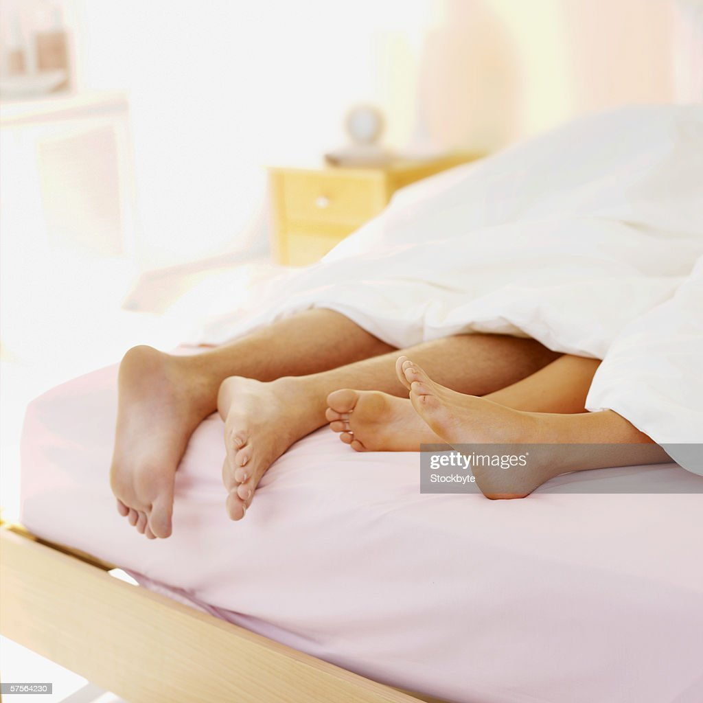 View of a couples' legs under a duvet : Stock Photo