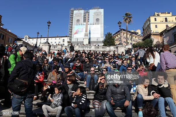 View of a crowd of people seated on the Spanish Steps Rome Italy April 7 2015 At the top of the steps covered in scaffolding is the Trinita dei Monti...