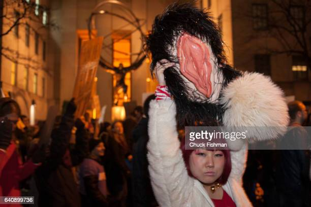 View of a demonstrator as she holds a model of a vagina over her head on Fifth Avenue across from the statue of Atlas during the Women's March on New...
