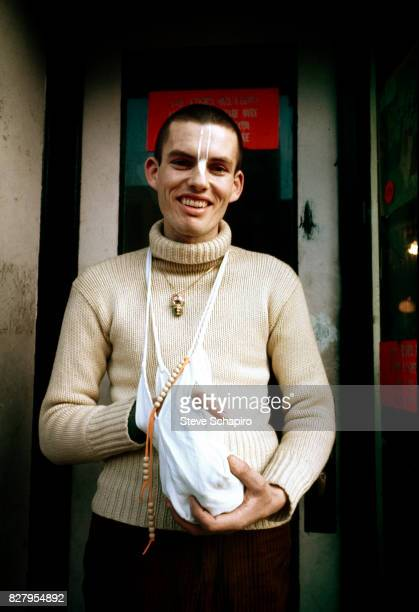 View of a devotee of the International Society for Krishna Consciousness better known as Hare Krishna as he stands outside a storefront temple New...