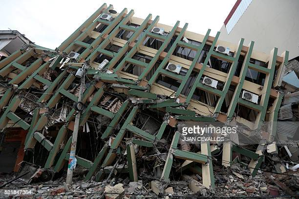 TOPSHOT View of a fallen building after a 78magnitude quake in Portoviejo Ecuador on April 17 2016 At least 77 people were killed when a powerful...