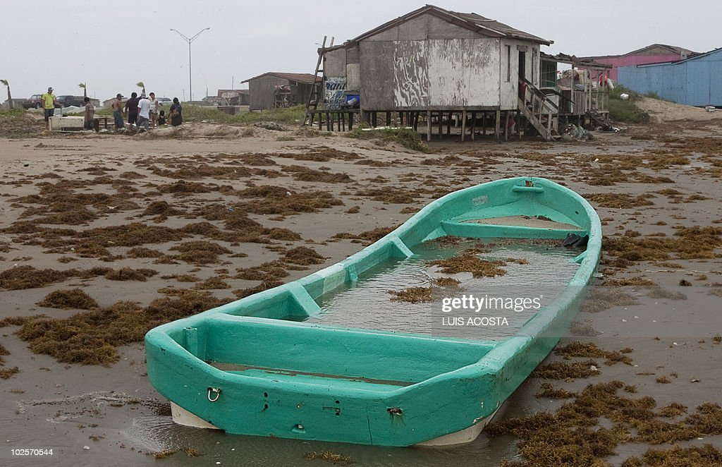 View of a fishing boat full of water on a beach after the passage of Hurricane Alex in Bagdad Beach, in Matamoros, Tamaulipas State, on July 1, 2010. Alex, the first hurricane of the Atlantic season, weakened across northeast Mexico as it neared high mountains on Thursday, after disrupting oil clean-up operations in the Gulf of Mexico. Alex was downgraded to a tropical storm after roaring ashore late Wednesday as a Category Two hurricane slightly south of the eastern US-Mexico border. AFP PHOTO/Luis Acosta