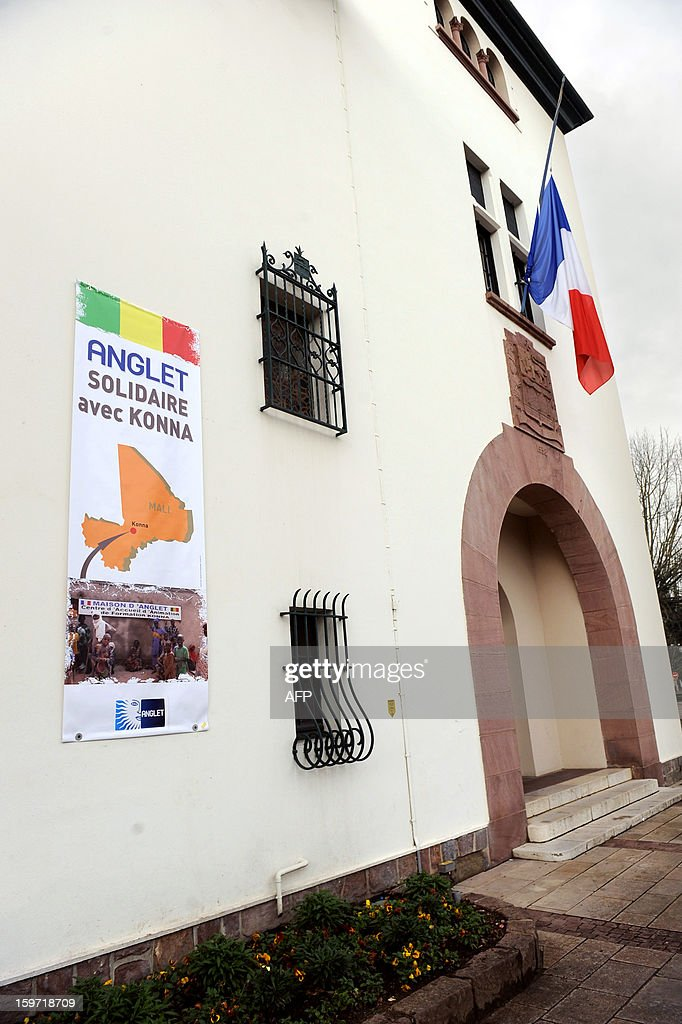 A view of a French flag flying half-mast at the town hall in Anglet, in the French Pyrenees-Atlantiques region, next to a sign reading 'Anglet: Solidarity with Konna (Mali)', on January 19, 2013, in honor of a French man who was killed in the hostage rescue operation at a remote gas plant seized by Islamist militants in Algeria. Yann Desjeux, 52, who was a former member of the French special forces at the 1st RPIMA in Bayonne, in southwestern France, owned a restaurant, in Anglet. AFP PHOTO GAIZKA IROZ