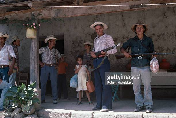 View of a group of local militia and residents as they stand under a porch in a village in territory controlled by Popular Revolutionary Forces...