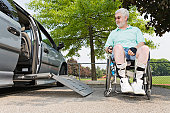 Man in a wheelchair coming out from a wheelchair accessible vehicle