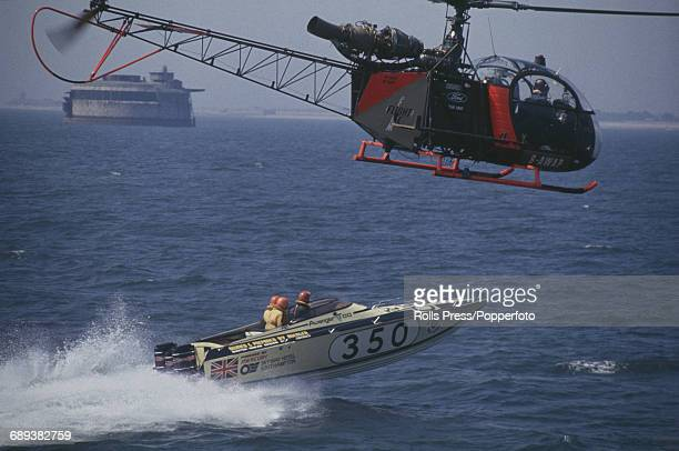 View of a helicopter following Finnish rally driver Timo Makinen and fellow crew members Pascoe Watson and Brian Hendicott as they pass Portsmouth...