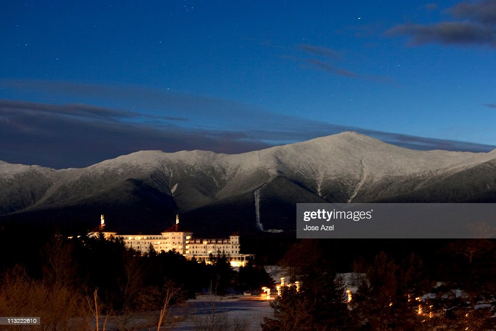 View of a hotel at night,  in front of a snow capped Mount Washington in the White Mountains of New Hampshire.