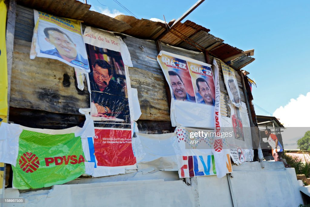 View of a house covered with posters of Venezuelan President Hugo Chavez at San Agustin shantytown in Caracas on January 4, 2013. Hugo Chavez's top aides have gone on the offensive, accusing the opposition and media of waging a 'psychological war,' as Venezuela's cancer-stricken president battles a serious lung infection. The closing of ranks followed a high-level gathering of top Venezuelan officials in Havana with Chavez, amid growing demands to know whether he will be fit on January 10 to take the oath of office for another six-year-term. AFP PHOTO/Leo Ramirez
