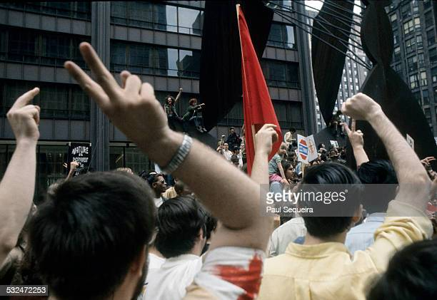 View of a large crowd gathered around the Picasso sculpture in Daley Plaza during a peace march Chicago Illinois 1970