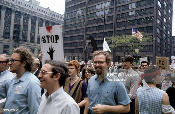 View of a large crowd of protestors marching past Daley Plaza and the Picasso sculpture towards Grant Park during a peace rally protesting the deaths...
