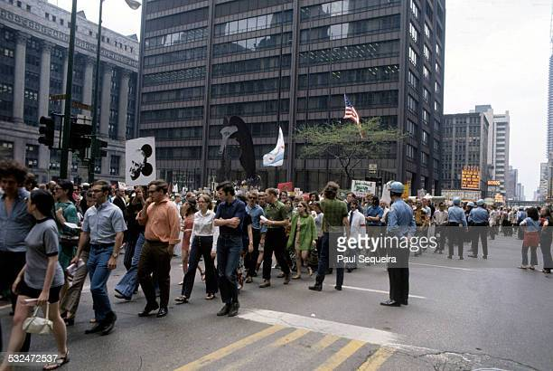 View of a large crowd of protestors marching past Daley Plaza and the Picasso sculpture on Dearborn Avenue towards Grant Park during a peace rally...