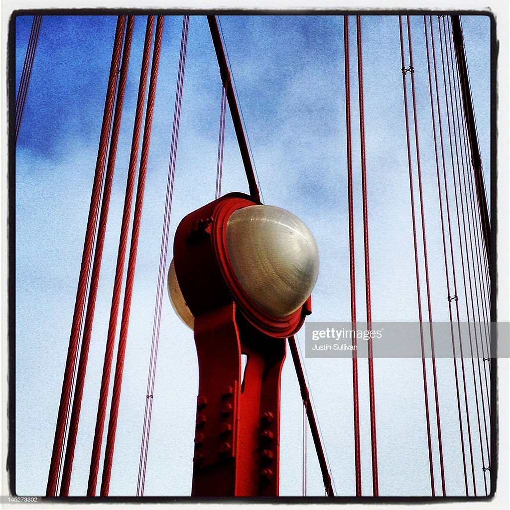 A view of a light fixture and suspender cables on the Golden Gate Bridge on May 3, 2012 in San Francisco, California. The Golden Gate Bridge, Highway and Transportation District is preparing for the 75th anniversary of the iconic Golden Gate Bridge that will be marked with a festival on May 26 - 27 that will feature music, displays of bridge artifacts and art exhibits. The 1.7 mile steel suspension bridge, one of the modern Wonders of the World, opened to traffic on May 27, 1937.