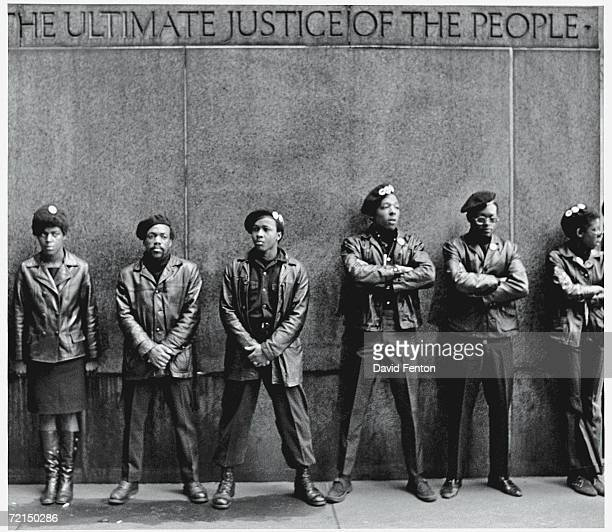 View of a line of Black Panther Party members as they stand outside the New York City courthouse under a portion of an Abraham Lincoln quote which...