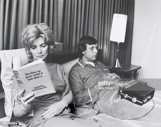 View of a male and female couple in bed 1960s The woman is reading a book titled 'Everything You Always Wanted To Know About Sex' while the man is...