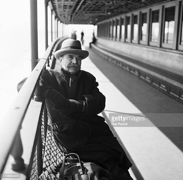 View of a male passenger on the Staten Island ferry sitting on a bench on the deck and leaning on the railing New York New York 1948 He has a...