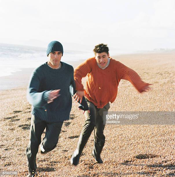 view of a man outrunning another on the beach