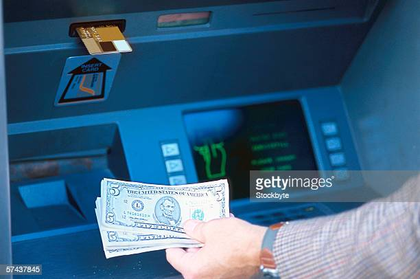 view of a man withdrawing money at an automatic transaction machine