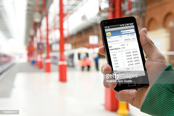 A view of a man's hand as he uses a Samsung Galaxy S II smartphone at a London train station during a shoot for Android App Guide June 15 London
